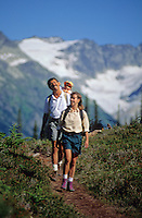 Baby in backpack pulls Dad's ear as the family hikes Whistler Mountain.