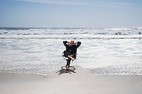 Senior business man sitting on office chair on beach elevated view