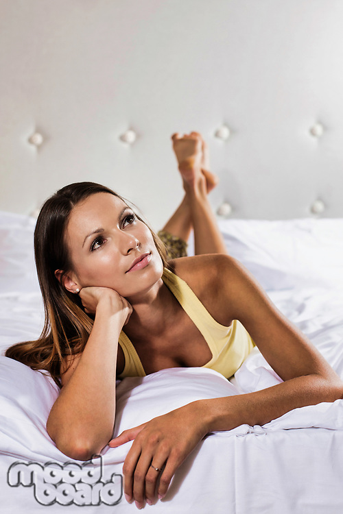 Portrait of young thoughtful attractive woman lying in bed