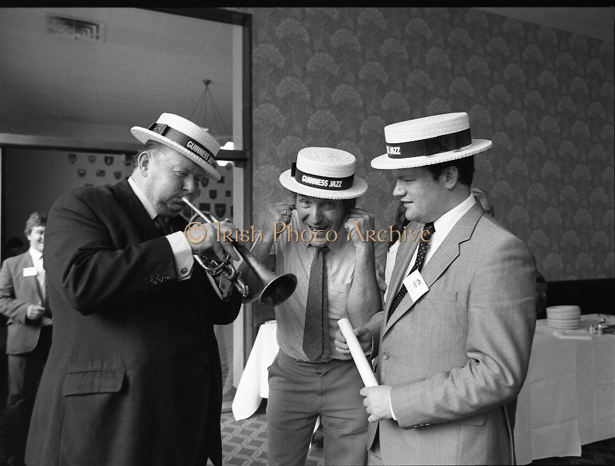 """Guinness Jazz Festival, Cork.01/07/1982  ..Topping the bill at the festival were,The First Lady of Jazz, """"Ella Fitzgerald"""",The legendary """"B.B.King"""" and the unique """"Modern Jazz Quartet""""..At the reception Mr Bobby Howick, Trade Director Guinness Group Sales, tries out the trumpet of Mr Pieter Sluis (centre){but not very well}..Mr Sluis is a member of The Bruxelles Jazz Group,who played at the reception. Also pictured is Mr Jim Mountjoy, Metropole Hotel, Cork. Mr Mountjoy is a Co-festival Director."""