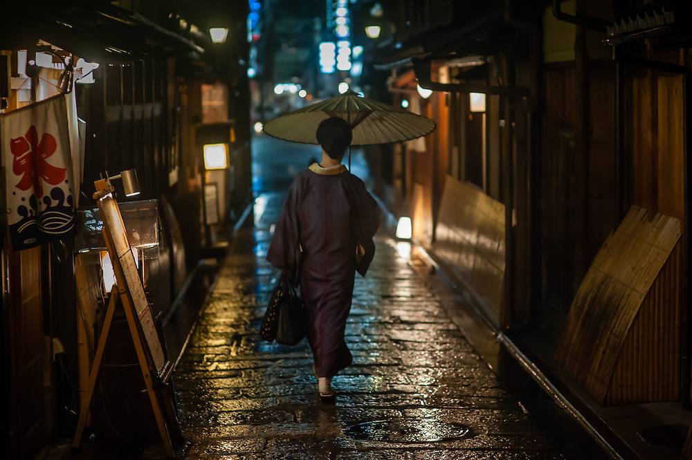 Woman in kimono and umbrella under the rain in Gion district (Kyoto, Japan)