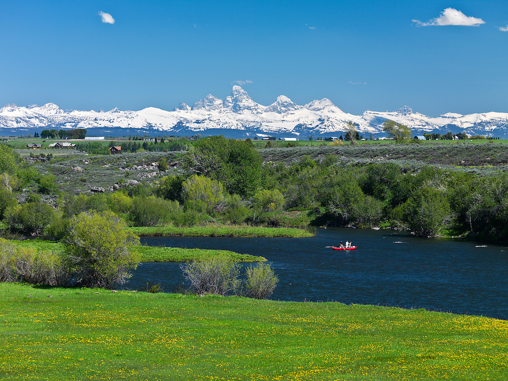 Two people float down the Henrys Fork of the Snake River near Ashton, Idaho on a perfect summer day with the snow covered Teton Mountain Range in background