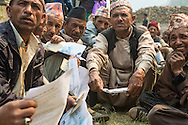 Homeowners from Dolakha, many who traveled over three hours by foot, lineup to receive the first installment, Rs 50,000 of the promised Rs200,000 to rebuild their homes, at a makeshift facility, near the  Singati Bazaar in Dolakha, Nepal  April 13, 2016. Less than one-tenth of a percent, approximately 700 of the 770,000 owners of the affected households, have received cash grants from the government to rebuild their homes.  <br /> Gurkha was one of the hardest hit areas, including the Singati Bazaar, where over 100 bodies were buried under the ruble following the 7.8 magnitude April 25, 2015 earthquake and May 12th aftershock. Singati was the major market for residents of 21 Village Development Committees and many survivors of the April 25th earthquake were in the bazaar buying supplies when the aftershock hit causing a huge landslide.<br /> &copy; 2016 Michelle McLoughlin