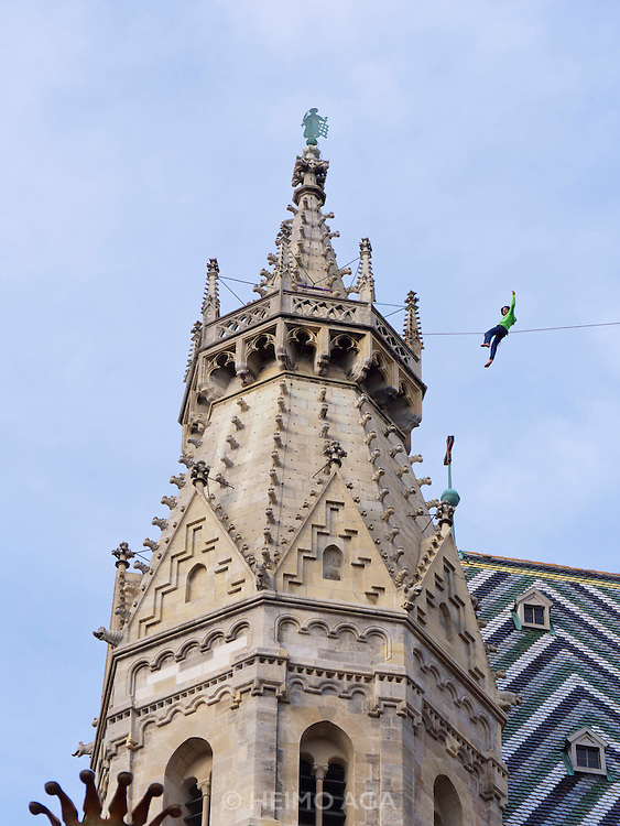 """Vienna, Austria. The """"Walk am Dom"""" is the highlight of St. Stephen's fair (Steffl-Kirtag) at the beginning of the """"Long Night of Churches"""" (Lange Nacht der Kirchen..Slackliner Christian Waldner crosses between St. Stephen's South Tower """"Steffl"""" to the Heidenturm and back - on a one inch wide slack line in a height of 60 meters.."""