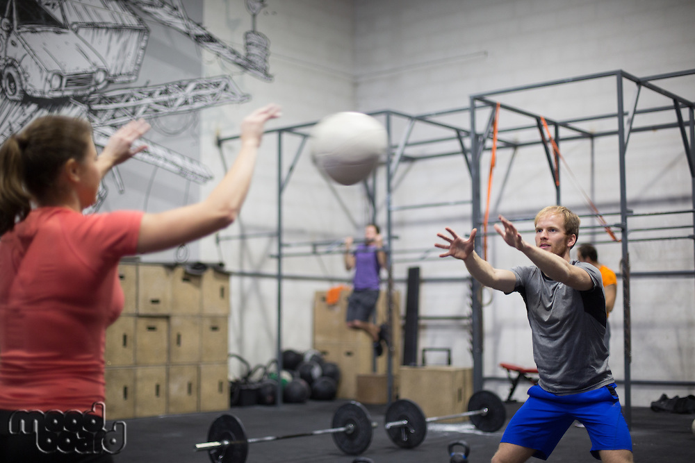 Man throwing medicine ball towards woman in crossfit gym