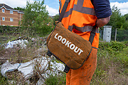 Lookout written on a bag held by a man dressed in high-visibility work clothes at Aldershot Railway Station, Hampshire, UK.  (photo by Andrew Aitchison / In pictures via Getty Images)