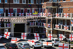 Outnumbered but hoping for victory, A Colombian family and their dog Troy are pictured on the Kirby Estate in Southwark where local residents have put on a huge display of support for England in the World Cup. PICTURED: Son Jean-Paul Jhonnes, 19, and his mother Mother Sandra Ramos, 48, outside their second floor flat, surrounded by England flags . London, July 02 2018.