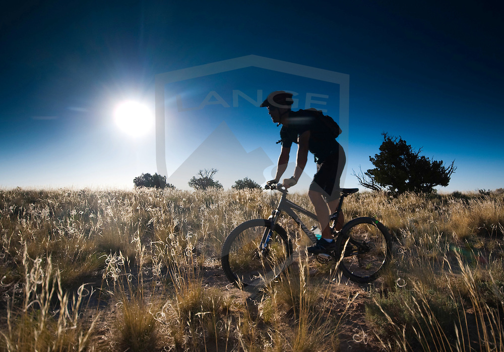 mountain biker cliff youngberg makes his way across the grass filled desert landscape while the morning sun rises higher at the white mesa bike trails, new mexico