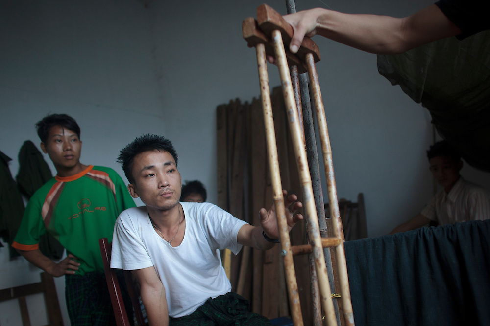 Kachin's militia member Lalaw Ze Dai, from Waimaw village, 25, catch his crutches in the General Military Hospital in Laiza village close to the China border, Myanmar on July 26, 2012. He was injured by a landmine in June, 26, 2012 loosing part of his right leg on top of knee.