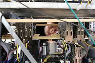 Inside the Alpereum mine, Nicolai Oster is making some adjustments to the drives / Dans la mine Alpereum, Nicolai Oster ajuste des cables derrière des cartes mères.