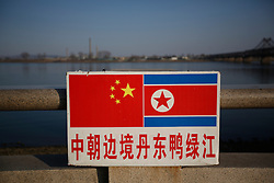 The Chinese and North Korean national flags are seen on a sign along the Yalu River where across is the North Korean town of Sinuiju in Dandong, Liaoning Province, China on 07 April 2013. China on 07 April said its embassy in Pyongyang was still 'operating normally' following North Korea's warning to diplomats that it could only guarantee their safety until Wednesday. Beijing had asked North Korea to protect the safety and interests of Chinese citizens and businesses in the country.