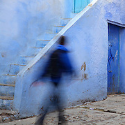 Boy walking in a narrow street painted blue with steps leading up to the door of a house, in the medina or old town of Chefchaouen in the Rif mountains of North West Morocco. Chefchaouen was founded in 1471 by Moulay Ali Ben Moussa Ben Rashid El Alami to house the muslims expelled from Andalusia. It is famous for its blue painted houses, originated by the Jewish community, and is listed by UNESCO under the Intangible Cultural Heritage of Humanity. Picture by Manuel Cohen