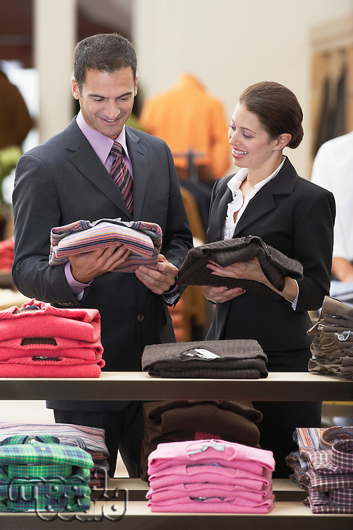 Salesperson assisting businessman in clothes store
