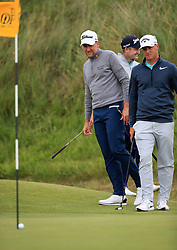 England's Ian Poulter (left) and Sweden's Alex Noren (right) look at Scotland's Russell Knox's (centre) putt as the ball rests on the flag during day two of The Open Championship 2017 at Royal Birkdale Golf Club, Southport.