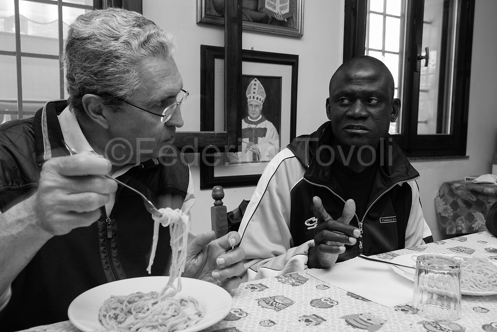 Maniame Bathily belonging from Mali: hosted by Caritas of Modena dioocese in a Casa della Carità in the counryside nearby te city.. Lunch with his tutor in the great table of the House of Charity where she lives.