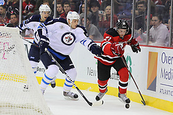 Jan 17; Newark, NJ, USA; Winnipeg Jets defenseman Randy Jones (12) and New Jersey Devils left wing Mattias Tedenby (21) battle for the loose puck during the second period at the Prudential Center.