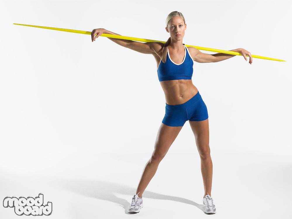 Female athlete holding javelin behind shoulders