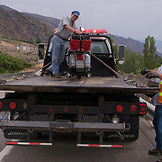 "Robert ""Doc"" Morgan with his Vespa P200E loaded onto a flatbed truck by the side of US Highway 2 near Wenatchee, Washington"