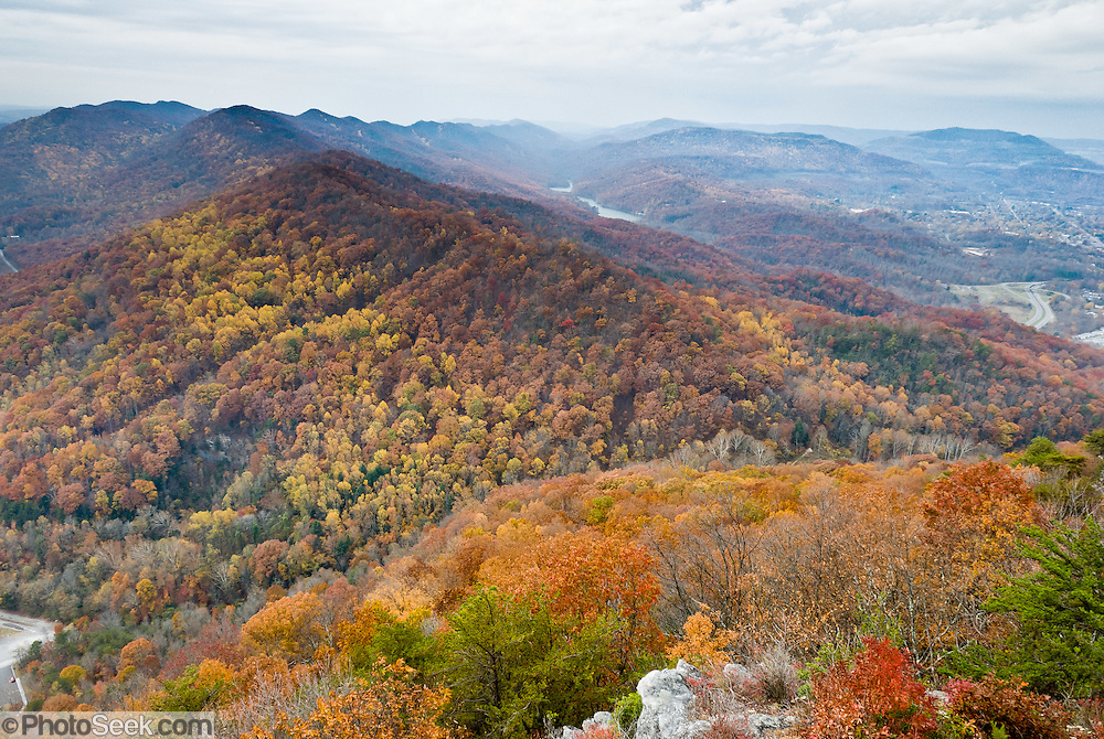 Orange and yellow fall foliage colors brighten Cumberland Gap National Historic Park in early November, above the town of Cumberland Gap, Tennessee. Tristate Peak rises to 1990 feet elevation on the upper left, where the states of Kentucky, Tennessee, and Virginia meet, as resolved in 1803. Cumberland Gap (elevation 1600 feet / 488 meters) is a pass through the Cumberland Mountains region of the Appalachian Mountains, also known as the Cumberland Water Gap.