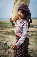 BAGAN, MYANMAR - CIRCA DECEMBER 2013: Young Burmese woman carrying a bag with sand in a village near Bagan