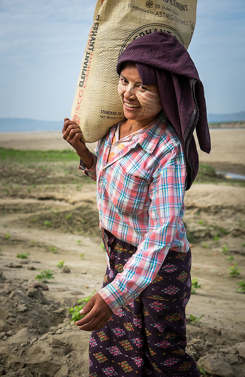 BAGAN, MYANMAR - CIRCA DECEMBER 2013: Young Burmese woman carrying a bag with sand in a village near Bagan
