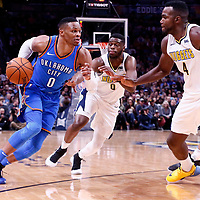 09 November 2017: Oklahoma City Thunder guard Russell Westbrook (0) drives past Denver Nuggets guard Emmanuel Mudiay (0) and faces Denver Nuggets forward Paul Millsap (4) during the Denver Nuggets 102-94 victory over the Oklahoma City Thunder, at the Pepsi Center, Denver, Colorado, USA.