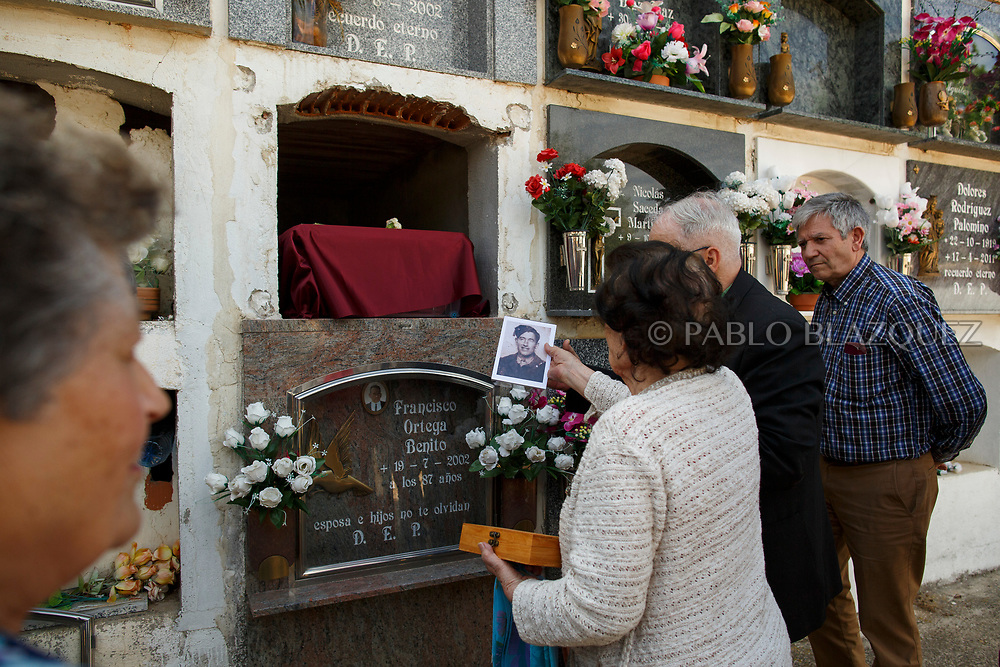 19/05/2018. Carmen Benito Alcantarilla (2L) holds a picture of his uncle Valentin Alcantarilla Mercado who was assassinated by dictator Francisco Franco's forces as his remains are placed inside a niche during his burial at the cemetery on May 19, 2018 in Sacedon, Guadalajara province, Spain. General Franco's forces killed Timoteo Mendieta and other people between 1939 and 1940 after Spain's Civil War and buried them in mass graves in Guadalajara's cemetery. Argentinian judge Maria Servini used the international human rights law and ordered the exhumation and investigation of Mendieta's mass grave. The exhumation was carried out by Association for the Recovery of Historical Memory (ARMH) recovering 50 bodies from 2 mass graves and identified 24 of them. Spain's Civil War took the lives of thousands of people on both sides, but Franco continued his executions after the war has finished. Spanish governments has never done anything to help the victims of the Civil War and Franco's dictatorship while there are still thousands of people missing in mass graves around the country. (© Pablo Blazquez)