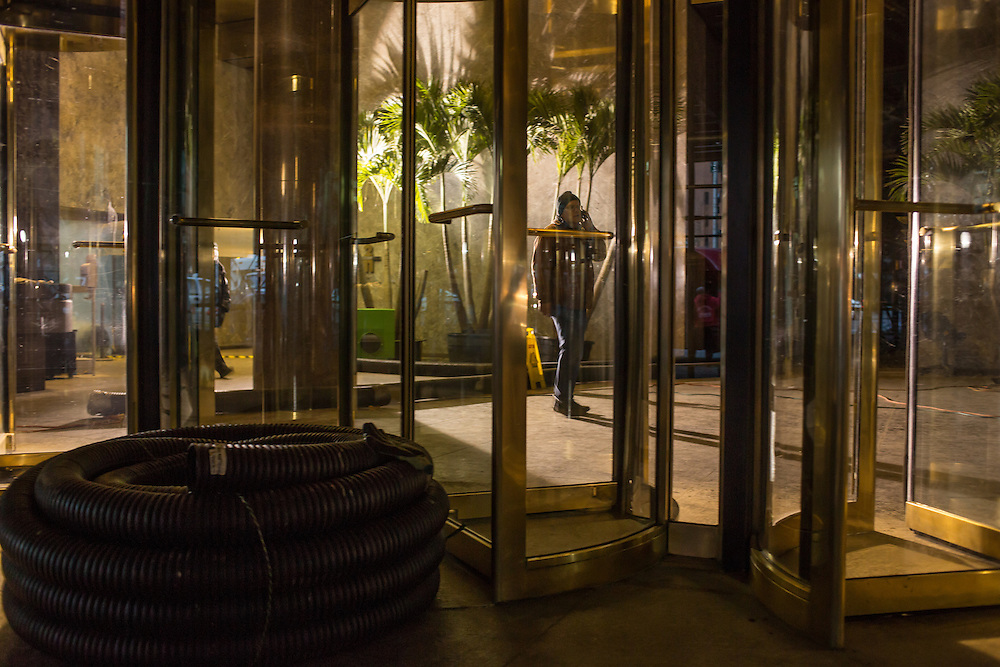 A recovery worker talks on his mobile phone inside the eerily-lit lobby on the Whitehall Street side of One State Street Plaza. A coiled length of corrugated drainage hose remains outside.