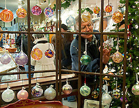 Fred Metting admires colorful glass ornaments hung in the window of Capitol Craftsman and Romance Jewelers during Midnight Merriment Friday evening.  (Karen Bobotas/for the Concord Monitor)