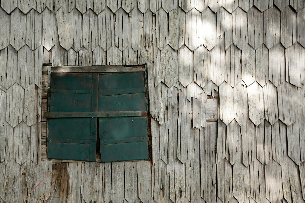 Green metal shutters and the traditional wooden tiles exterior at Tise mountain hut, 1380m, Čvrsnica, Bosnia and Herzegovina.