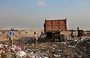 New Delhi, India - <br /> <br /> Garbage Mountain<br /> <br /> Just a few miles from the famous Akshardham temple, where tourists flock to see the structure's sandstone and marble work, the 29-hectare, slum-surrounded Ghazipur landfill in east Delhi seems a world apart. Each day hundreds of mainly migrant workers earn a meager living at the landfill by collecting recyclable material like plastic, metal and even hair to sell. The dump is the last port of call for Delhi's trash, having already been picked through by other waste collectors who collect bags of garbage directly from homes. Delhi is home to three landfills where around 6,000 tons of trash is dumped daily. Studies have shown that living near a landfill increases the risk of cancer, birth defects and asthma.<br /> <br /> Photo shows: Young rag pickers chase the garbage truck to collect recyclables at the Ghazipur landfill.<br /> &copy;Chinky Shukla/Exclusivepix Media