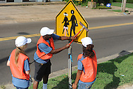Youth Corps' D'Marius Deberry (center), Dakota Hensley (left) and Erika Sisk clean traffic signs in Oxford, Miss. on Tuesday, June 25, 2013.