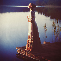 Female youth wearing period costume dress standing alone beside lake on wooden jetty