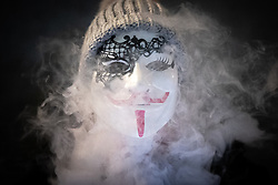 © Licensed to London News Pictures . 05/11/2019. London, UK. A woman blows vape smoke through her mask . Supporters of Anonymous , many wearing Guy Fawkes masks , attend the Million Mask March bonfire night demonstration , in Trafalgar Square in central London . Photo credit: Joel Goodman/LNP