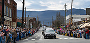 A crowd of people line the street in Black Mountain, N.C. to view and honor the hearse carrying the body of Rev. Billy Graham as it travels from the Billy Graham Training Center at the Cove in Asheville, N.C. to the Billy Graham Library in Charlotte. N.C.on Saturday, Feb. 24, 2018. (AP Photo/Kathy Kmonicek)