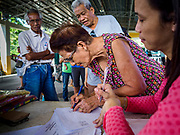 21 JANUARY 2018 - CAMALIG, ALBAY, PHILIPPINES: A woman signs for relief supplies she received at the Barangay Cabangan evacuee shelter in a school in Camalig. There are about 650 people living at the shelter. They won't be allowed to move back to their homes until officials determine that Mayon volcano is safe and not likely to erupt, which could take at least two more weeks. More than 30,000 people have been evacuated from communities on the near the Mayon volcano in Albay province in the Philippines. Most of the evacuees are staying at schools in communities outside of the evacuation zone.   PHOTO BY JACK KURTZ