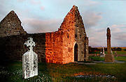 Low angle view of Clonmacnoise Cathedral, 10th century, with the Cross of the Scriptures (replica), 10th century, on the right, Clonmacnoise, County Offaly, Ireland, at sunset. Clonmacnoise was founded by St Ciaran, with the help of Diarmait Ui Cerbaill, Ireland's first Christian King. The site presents the largest collection of Early Christian graveslabs in Western Europe. Picture by Manuel Cohen