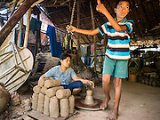 30 OCTOBER 2015 - TWANTE, MYANMAR: A woman and son craft pots in the potters' village in Twante, (also spelled Twantay) Myanmar. Their potters' wheel is hand powered. The boy kicks the wheel to spin it while the woman makes the pots. Twante, about 20 miles from Yangon, is best known for its traditional pottery. The pottery makers are struggling to keep workers in their sheds though. As Myanmar opens up to outside investments and its economy expands, young people are moving to Yangon to take jobs in the better paying tourist industry or in the factories that are springing up around Yangon.     PHOTO BY JACK KURTZ