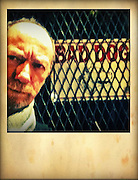 mean looking man in front of fence with Bad Dog sign at night cellphone photography,Iphone pictures,smartphone pictures