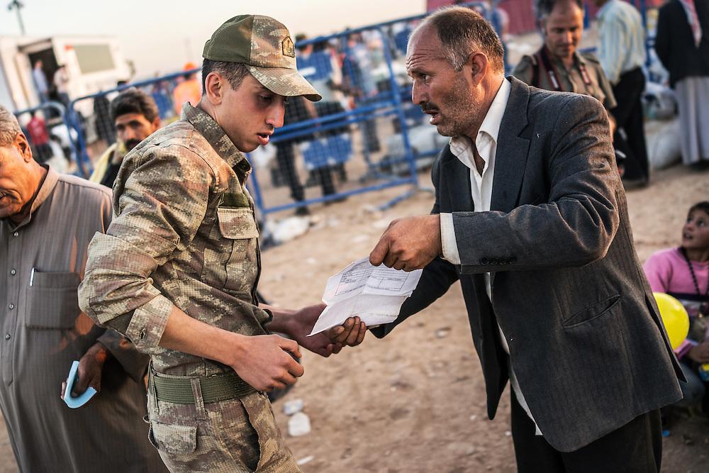 am man showing his permit to enter turkey border to the army officer at Yumurtulik border suruc, Sanliurfa