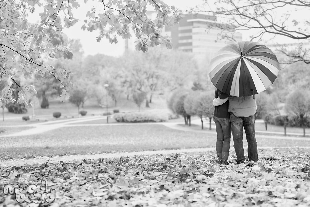 Black and white photo of man holding umbrella while enjoying the lovely view with his wife in park