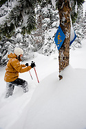 Side view of a mid adult woman in snowshoes with ski poles walking past a snowshoe trail sign in deep powder in Bend, Oregon. (releasecode: jk_mr1034) (Model Released)