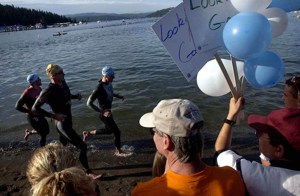 JEROME A. POLLOS/Press..Supporters cheer on Ironmen as they make their way down City Beach to start their second lap of the swim.