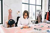 """ROME, ITALY - 15 OCTOBER 2018: Caterina (21), a seamstress who trained at the Massoli Accademy and is currently employed by FENDI after an inernship, works on a FENDI Haute Couture dress during the LVMH Journées Particulières exhibition at the Fendi headquarters in Rome, Italy, on October 15th 2018.<br /> <br /> The LVMH Journées Particulières is is a series of exhibitions that show the creations and history of the LVMH fashion houses. The driving theme behind the Journées Particulières is to allow the general public to discover the inner workings of the Houses which are part of the LVMH heritage.The LVMH Journées Particulières exhibition by fashion house FENDI takes place at their headquarters at the Palazzo della Civiltà Italiana, also called the """"Colosseo Quadrato"""" (Square Colosseum),  an outstanding jewel of the 20th century Roman architecture."""