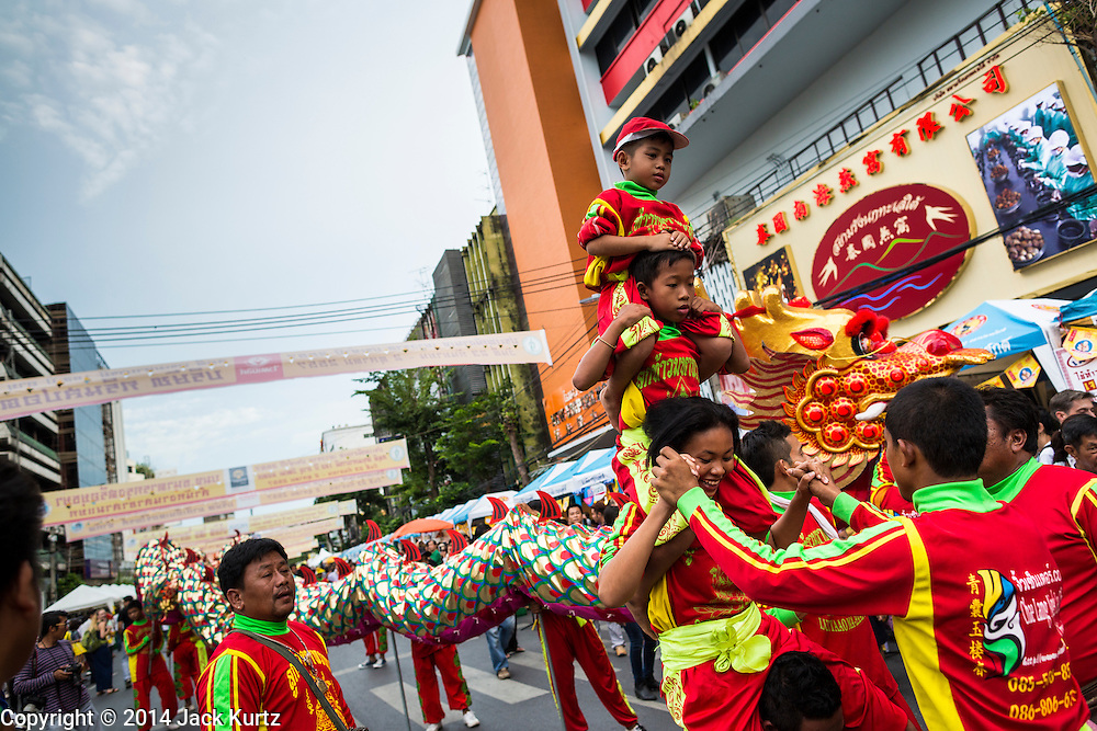 24 SEPTEMBER 2014 - BANGKOK, THAILAND: A youth acrobat troupe performs on the street during the Vegetarian Festival Parade in Bangkok. The Vegetarian Festival is celebrated throughout Thailand. It is the Thai version of the The Nine Emperor Gods Festival, a nine-day Taoist celebration beginning on the eve of 9th lunar month of the Chinese calendar. During a period of nine days, those who are participating in the festival dress all in white and abstain from eating meat, poultry, seafood, and dairy products. Vendors and proprietors of restaurants indicate that vegetarian food is for sale by putting a yellow flag out with Thai characters for meatless written on it in red.    PHOTO BY JACK KURTZ