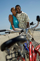 Couple with bicycles embracing on wall (portrait)
