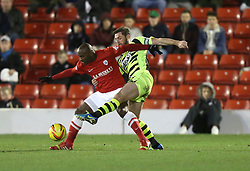 Yeovil Town's Jamie McAllister and Barnsley's Jason Scotland battle for the ball - Photo mandatory by-line: Matt Bunn/JMP - Tel: Mobile: 07966 386802 14/12/2013 - SPORT - Football - Barnsley - Oakwell - Barnsley v Yeovil Town - Sky Bet Championship