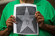 A member of a coalition of black civil-rights advocates holds a picture with a star of Bill Cosby during a news conference on July 9, 2015 in Los Angeles, California. The group calls onto the Hollywood Chamber of Commerce President Leron Gubler to remove Bill Cosby's star on the Hollywood Walk of Fame. (Photo by Ringo Chiu/PHOTOFORMULA.com)