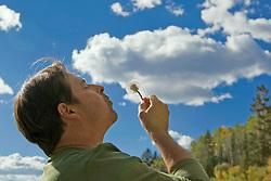 man blowing a milkweed towards the sky in Santa Fe