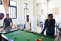 Marsa, Malta - 17 August, 2012: Sub-saharan migrants play pool in one of the recreation rooms of the Marsa Open Centre, in Marsa, Malta,  on 17 August, 2012.<br /> <br /> The Marsa Open Centre's capacity is of 650 people, most of which are from Somalia. The centre's popoulation is composed of immigrants who received subsidary protection, asylum seekers (immigrants who applied and wait for their case to be handled), and rejected asylum seekers.<br /> <br /> The Open Centres in Malta serve as a temporary accomodation facility, but they ended becoming permanent accomodation centres.  All immigrants who enter in Malta illegally are detained. Upon arrival to Malta, irregular migrants and asylum seekers are sent to one of three dedicated immigration detention facilities. Once apprehended by the authorities, immigrants remain in detention even after they apply for refugee status. detention lasts as long as it takes for asylum claims to be determined. This usually takes months; asylum seekers often wait five to 10 months for their first interview with the Refugee Commissioner. Asylum seekers may be detained for up to 12 months: at this point, if their claim is still pending, they are released and transferred to an Open Center. The migrants who do not receive neither refugee status of subsidiary protection are considered illegal, though living in the open centers. They end up living in Malta for months or years, while some go aboad illegally.<br /> <br /> Gianni Cipriano for The New York Times